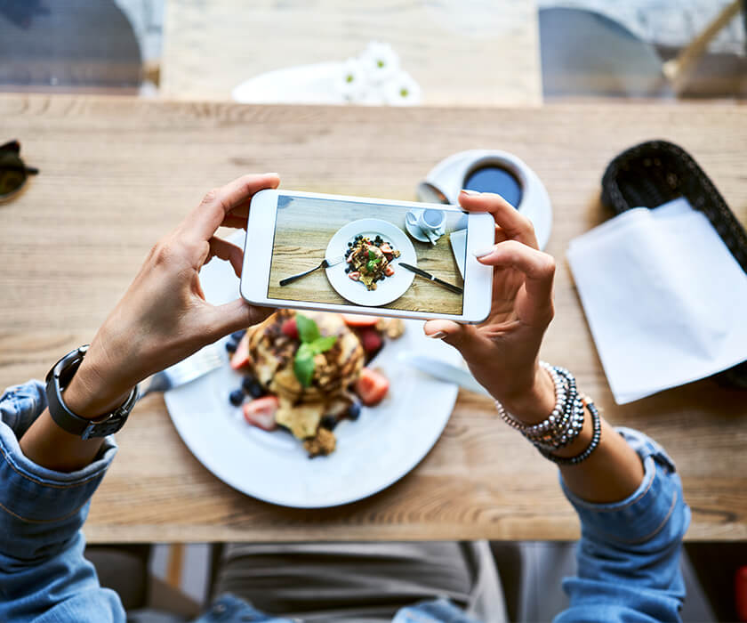 Women taking picture with an iPhone of a plate of pancakes placed on a wooden table